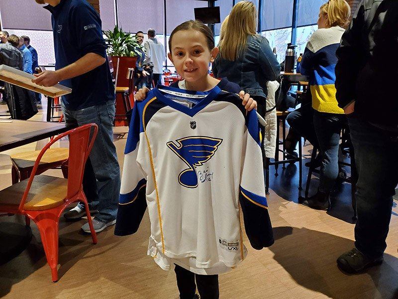 Girl holding signed jersey